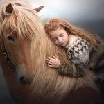 bambina sdraiata sul dorso di un cavallo